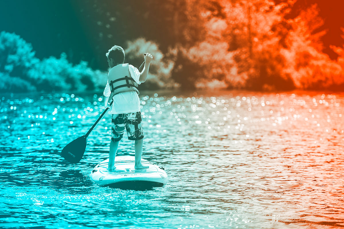 boy paddling while standing on raft